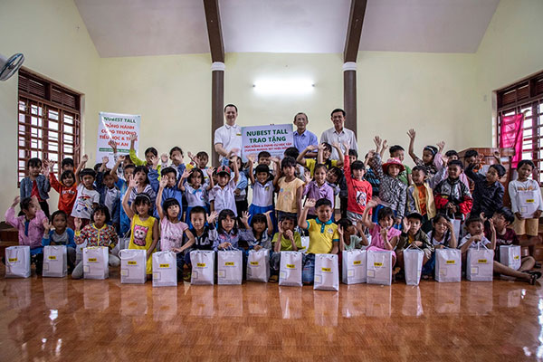 Đại diện NuBest Tall trao tặng học bổng cho các em học sinh dân tộc Co tại điểm nhà sàn truyền thống ở xã Bình An